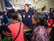 30 AUGUST 2016 - BANGKOK, THAILAND:  A volunteer directs people lined up for the food distribution on the last day of Hungry Ghost Month in Bangkok. Chinese temples and shrines in the Thai capital host food distribution events during Hungry Ghost Month, during the 7th lunar month, which is usually August in the Gregorian calendar.        PHOTO BY JACK KURTZ