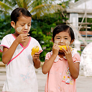 Two burmese girls eating corn