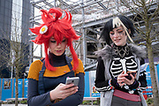 Girls on their smartphones dressed up for a day out in their Cosplay guises Nao Egokoro with red hair and Reko Yabusame, from the video game Your turn to die on 14th March 2020 in Birmingham, United Kingdom. Cosplay or costume play, is a performance art in which participants called cosplayers wear costumes and fashion accessories to represent a specific character. Cosplayers often interact to create a subculture, and a broader use of the term applies to any costumed role-playing in venues apart from the stage. Favorite sources include anime, cartoons, comic books, manga, television series, and video games.