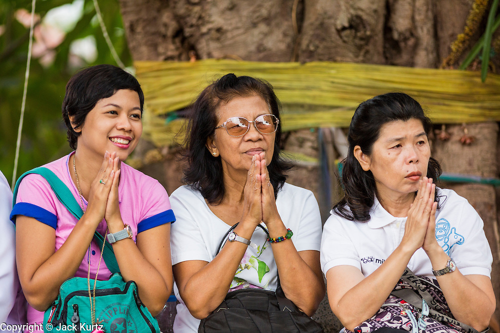 29 JUNE 2014 - DAN SAI, LOEI, THAILAND: Women pray in front of the temple during a ceremony in Wat Ponchai on the last morning of the Ghost Festival. Phi Ta Khon (also spelled Pee Ta Khon) is the Ghost Festival. Over three days, the town's residents invite protection from Phra U-pakut, the spirit that lives in the Mun River, which runs through Dan Sai. People in the town and surrounding villages wear costumes made of patchwork and ornate masks and are thought be ghosts who were awoken from the dead when Vessantra Jataka (one of the Buddhas) came out of the forest. On the last day of the festival people participate in merit making ceremonies at the Wat Ponchai in Dan Sai and lead processions through town soliciting donations for the temple.    PHOTO BY JACK KURTZ