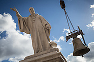 The statue of San Benedetto, born in Norcia in the main square of the town while a huge bell is removed from the Civic Tower