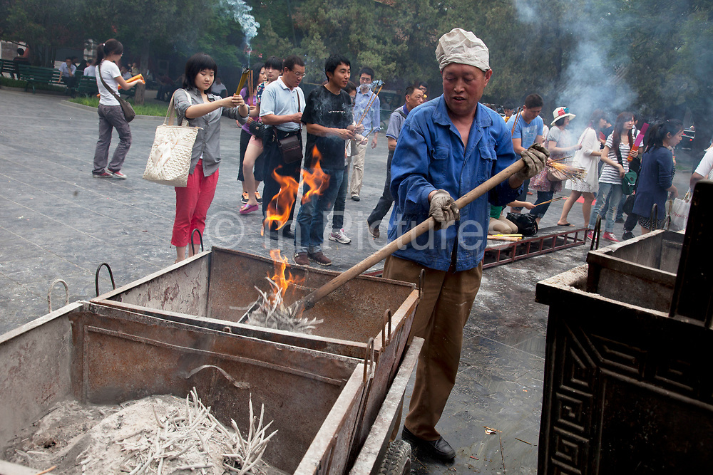 """Worker clears the burnt ashes from thousands of incense sticks which are burned at Yonghe Temple, also known as the """"Palace of Peace and Harmony Lama Temple"""", the """"Yonghe Lamasery"""", or - popularly - the """"Lama Temple"""" is a temple and monastery of the Geluk School of Tibetan Buddhism located in the northeastern part of Beijing, China. It is one of the largest and most important Tibetan Buddhist monasteries in the world. The building and the artworks of the temple is a combination of Han Chinese and Tibetan styles."""