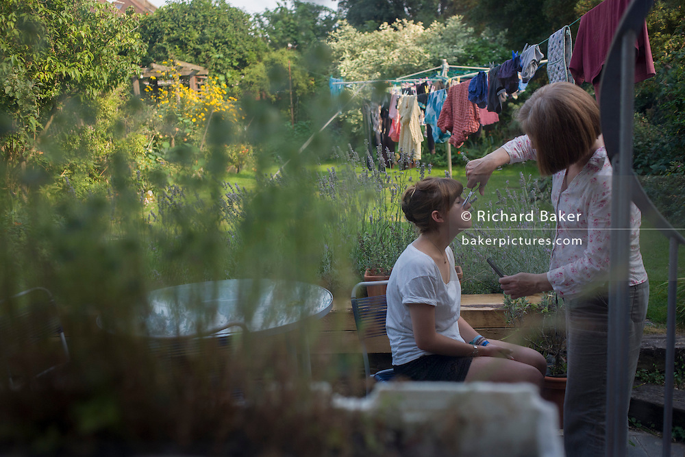 A mother trims the fringe of her teenage daughter in the family's back garden.