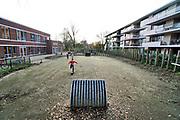 Nederland, Nijmegen, 10-12-2019 Op last van de rechter heeft de gemeente gisteren het voetbalveldje in de speeltuin achter basisschool de Buut, links op de foto, aangepast. De voorzieningenrechter bepaalde vorige maand dat het veld van basisschool De Buut mag blijven, maar dat de betonnen rand eromheen en de goaltjes moeten verdwijnen. Bewoners van de appartementen tegenover de school, rechts op de foto, hadden geklaagd vanwege overlast door spelende en voetballende kinderen. Een betonnen rand is nu weggehaald en vervangen door een aarden rand en het kunstgras moet vervangen worden. De school en het speelveldje, speeltuintje, stonden er al lang voordat hier de appartementen waar veelal oudere pensionados in wonen, gebouwd werden . Na 18.30 mag er ook niet meer gespeeld worden. Foto: Flip Franssen