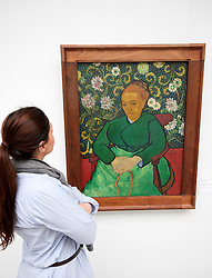 Woman looking at painting La Berceuse (Portrait of Madame Roulin) by `Vincent van Gogh at Kroller-Muller Museum in The Netherlands