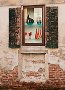 """Glass art in window display. Venice (Venezia) is the capital of Italy's Veneto region, named for the ancient Veneti people from the 10th century BC. The romantic """"City of Canals"""" stretches across 117 small islands in the marshy Venetian Lagoon along the Adriatic Sea in northeast Italy, Europe. The Republic of Venice wielded major sea power during the Middle Ages, Crusades, and Renaissance. Riches from Venice's silk, grain, and spice trade in the 1200s to 1600s built elaborate architecture combining Gothic, Byzantine, and Arab styles. Venice and the Venetian Lagoon are honored on UNESCO's World Heritage List."""