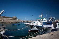 Pescherecci ormeggiati nel porto di Gallipoli (LE), di fronte al Rivellino, mentre una piccola barca da pesca a motore esce in mare.