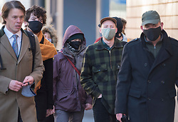 © Licensed to London News Pictures; 25/01/2021; Bristol, UK. Colston Four at court. SAGE WILLOUGHBY (second left in dark coat), MILO PONSFORD (middle in baseball cap with green face mask) arrive at Bristol magistrates court. Defendants Rhian Graham, 29, Milo Ponsford, 25, Jake Skuse, 32, and Sage Willoughby, 21, are due before Bristol Magistrates' Court for their first hearing today. They have been charged with criminal damage in connection with damage to the statue of slave trader Edward Colston which was pulled down during a Black Lives Matter protest on June 7 2020 and then thrown into Bristol Harbour. Police launched an appeal to trace suspects after the event and ten people were located. Six people accepted a caution while four were referred to the CPS. The statue was later retrieved by Bristol City Council who say that the damage is costed at £3,750. Police have warned anyone planning to protest at the court hearing that they will be breaking the lockdown laws which prohibit public gatherings of more than two people to combat the Covid-19 coronavirus pandemic. Photo credit: Simon Chapman/LNP.