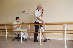 Prosthetist with elderly patient wearing belowknee (transtibial) limb; checking gait in mobility centre,