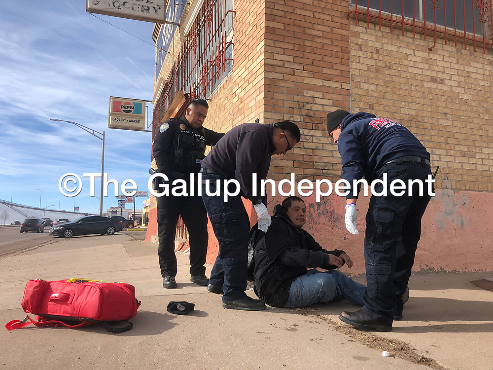 Gallup Police and Gallup Fire personnel help a man who identified himself to authorities as Brain Charley at the corner of Maloney Avenue and Fourth Street in Gallup Jan. 4. The man had been found passed out face down on the sidewalk.