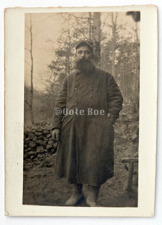 person with a large beard wearing a big coat standing in the woods 1900s