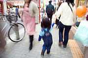 woman with a little child walking through a shopping street Japan Tokyo