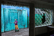 Woman walking by, praying in front of green wall,  Mawlamyine