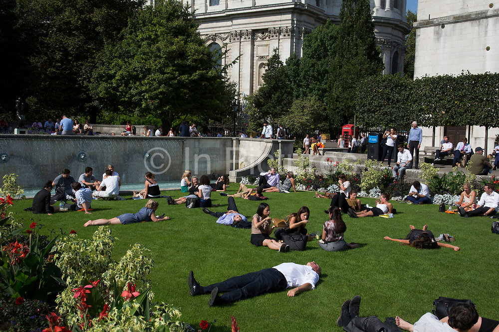 City workers lay about in the hot summer temperatures outside of St Pauls Cathedral in London, England, United Kingdom.