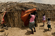 One of the family houses at the village. Newborn babies stay at home for 2-3 months before they are registered. In Angola?s Namibe desert, at Giraul, in the Namibe province, Tchikuteny, from the Mucubal tribe, is the leader of a big family, maybe the biggest family in the world.<br /> He is the chief leader, the manager and responsible for the entire village. <br /> In his village, Tchikuteny lives nowadays with most of his big family, his 33 wives, that were once 43, but 10 left the village, and most of their descendants.<br /> Tchikuteny maintains the registry of all the new-borns, totalizing 154 sons, and his grandsons, that are around 60. Nowadays, 4 new babies are on the way, and 3 great grand children were born recently.<br /> Huge harmony, love and respect transpire in the village atmosphere. The sense of a community is the pillar of their sustainability and sustenance and their autonomy depends prominently on cattle and agriculture that is made by the villagers. Nevertheless, Tchikuteny village is in close connection with their surrounding communities. Children attend Giraul School and there is proximity and relations with the extended family that lives in the surroundings.<br /> Being the spiritual leader of the community, Tchikuteny is also responsible for the weekly religious works that happens in the village church. <br /> This big family opened his doors to share with us their daily lives.