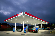 Esso garage forecourt at dusk with cars being filled with petrol and shop in background