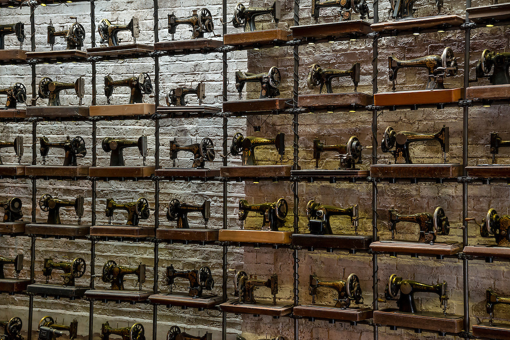 Old sewing machines create a wall of interest in a clothing store, in London