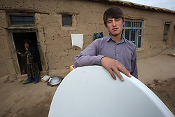 A boy, Sear, stands  beside the television receiver powered by Solar power that was installed as part of the NCA Solar Project, Khenjak Village, Shahrestan, Daikundi Province, Afghanistan.