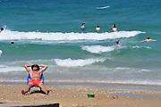 Israel, Haifa, Carmel Beach, Israelis go to the Beach on a warm, sunny  day. Man on chair sunbathing