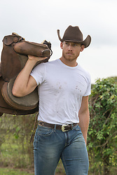 rugged cowboy carrying a saddle over his shoulder outdoors