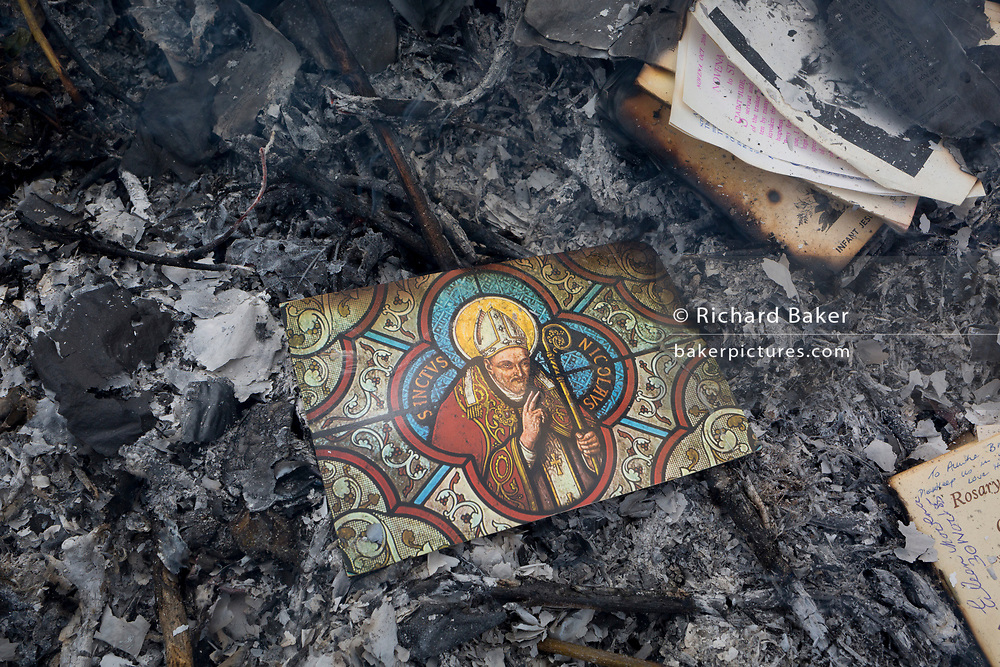 A postcard of patron Saint Nicholas, all that is left after the burning on a bonfire of religious mementoes, personal data, accounts records and general paperwork, on 30th July 2017, in Wrington, North Somerset, England. Saint Nicholas (270 – 343AD), was an historic 4th-century Christian saint.