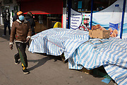 As the second week of the Coronavirus lockdown continues around the capital, and the UK death toll rising by 563 to 2,325, with 800,000 reported cases of Covid-19 worldwide, a masked shopper walks past a shop queue covered tables outside a corner shop in Brixton, on 1st April 2020, in London, England.