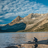 A photographer shoots dawn breaking over Bow Lake in Banff National Park, Alberta, Canada. Behind is  Mount Thompson.