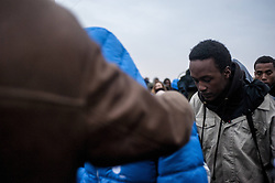 October 24, 2016 - Calais, France - Refugees arriving and waiting at the hangar of distribution of refugees with their luggage. The miners quickly pass into the hangar under the protection associations, in Calais, France on october 24, 2016. The dismantling of the jungle began Monday morning. Refugees come accompanied by the associations to the starting center ''C.A.O.''. Police frames the device. More than 850 press credentials were distributed. (Credit Image: © Julien Pitinome/NurPhoto via ZUMA Press)