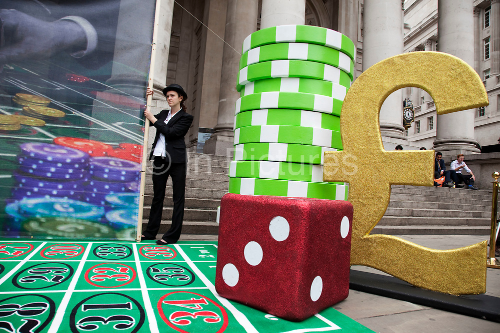 Robin Hood Tax supporters protest at the Royal Exchange near the Bank of England in the City of London. Campaigners today set up a giant roulette table in the City of London to protest against bankers' taking risky bets and lining their pockets with billions in a game where taxpayers had to bail them out when things went wrong. The giant casino board, complete with chips, roulette wheel and image from renowned artist Peter Kennard was in front of the Royal Exchange in the City from 12pm. Casino bankers' placed multi-billion pound bets in a game they were guaranteed to win. The tax would apply to speculative trade on financial products: stocks, bonds commodities and currency transactions. The Robin Hood Tax is a tiny tax of 0.05% on banks' financial transactions. Introduced globally, it would raise hundreds of billions of pounds every year for good causes.