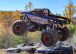 """Monster Truck """"Temporarily Insane"""", driven by Tyler Leicht, leaps over a line of cars during the Monstober monster truck/mudbog show at the Belknap County 4H fairgrounds on Saturday October 19, 2019.(Alan MacRae for the Laconia Daily Sun)"""