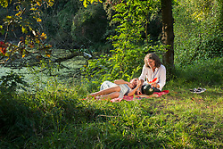 Couple having picnic and eating watermelon at riverbank, Bavaria, Germany