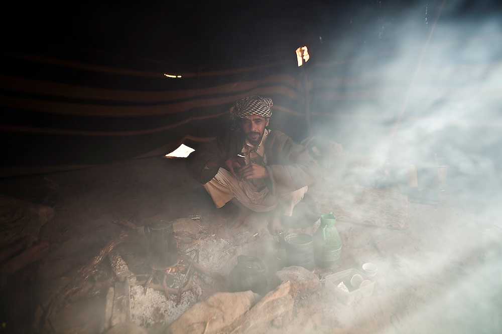 Bedouin guide Etzal Salem crouches by a smoky fire at his family's home in Wadi Rum, Jordan.