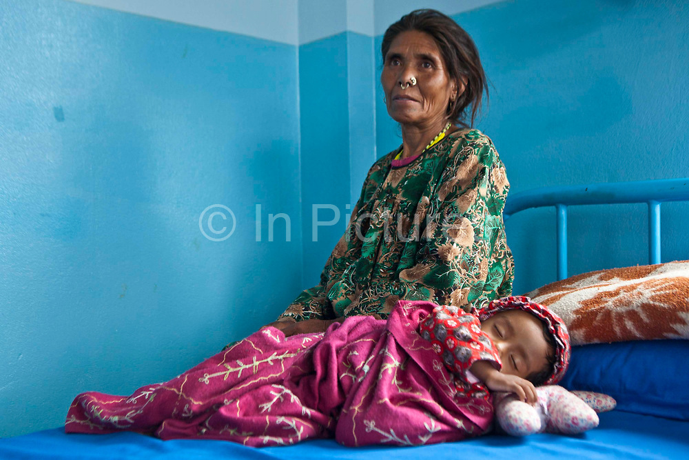 A small Nepalese baby lies sleeping on a hospital bed and his concerned grandmother sits next to him on a ward in the Friends of Needy Children Nutritional Rehabilitation Centre, Kathmandu, Nepal.  The child is 11-months old, but extremely small due to chronic malnutrition.  He arrived in the centre 1 week ago and has gained 600g in weight by receiving an intensive nutrition program.  Malnutrition prevents normal  growth and development.