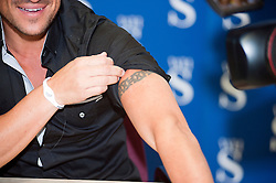 """Peter Andre shows a tatoo to one of his fans during a  book signing event for  his new childrens books """"The Happy Birthday Party"""" and """"A New Day at School"""" in WH Smiths Sheffield on 6th September 2011 .Image © Paul David Drabble"""