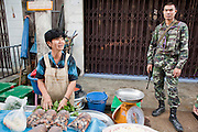 """Sept 25, 2009 -- PATTANI, THAILAND: A Thai soldier on duty in the morning market in Pattani, Thailand. Thailand's three southern most provinces; Yala, Pattani and Narathiwat are often called """"restive"""" and a decades long Muslim insurgency has gained traction recently. Nearly 4,000 people have been killed since 2004. The three southern provinces are under emergency control and there are more than 60,000 Thai military, police and paramilitary militia forces trying to keep the peace battling insurgents who favor car bombs and assassination.  Photo by Jack Kurtz / ZUMA Press"""