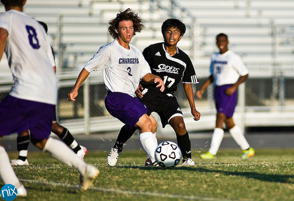 Cox Mill's Landon Rodriguez tries to get away from Concord's Noe Pliego during South Piedmont Conference soccer action Tuesday afternoon at Cox Mill High School in Concord. Cox Mill and Concord finished the game in an overtime tie.(Photo by James Nix)