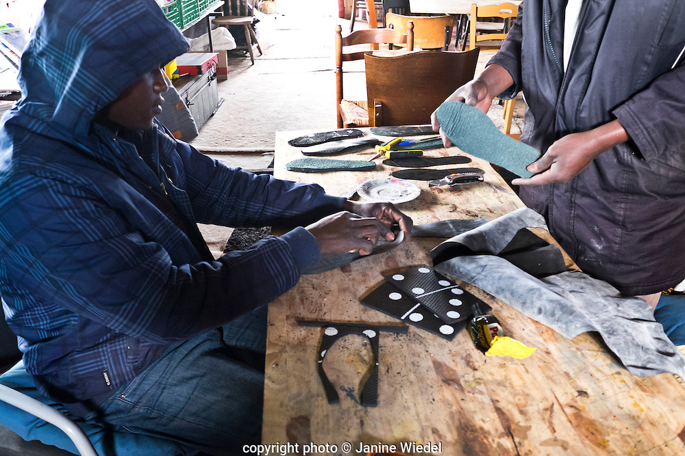 Learning to make shoes at the Ecole D'Art Metiers ( Technical training) in The Calais Jungle Refugee and Migrant Camp in France
