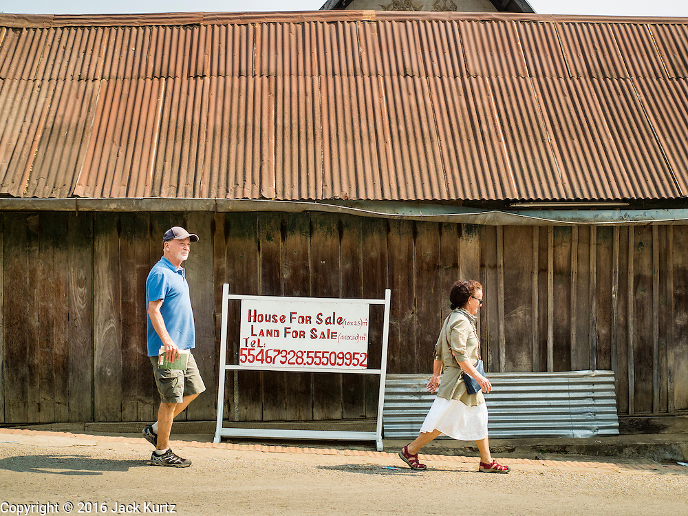 "13 MARCH 2016 - LUANG PRABANG, LAOS: Tourists walk past a home for sale in Luang Prabang. The for sale sign being in English indicates who the property is being marketed to. Luang Prabang was named a UNESCO World Heritage Site in 1995. The move saved the city's colonial architecture but the explosion of mass tourism has taken a toll on the city's soul. According to one recent study, a small plot of land that sold for $8,000 three years ago now goes for $120,000. Many longtime residents are selling their homes and moving to small developments around the city. The old homes are then converted to guesthouses, restaurants and spas. The city is famous for the morning ""tak bat,"" or monks' morning alms rounds. Every morning hundreds of Buddhist monks come out before dawn and walk in a silent procession through the city accepting alms from residents. Now, most of the people presenting alms to the monks are tourists, since so many Lao people have moved outside of the city center. About 50,000 people are thought to live in the Luang Prabang area, the city received more than 530,000 tourists in 2014.    PHOTO BY JACK KURTZ"