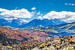 Colorado's Cimerron Valley in autumn. I love the juxtaposition of the lower elevation hills of the lower valley's red oak of autumn against the higher elevation aspen groves.  Of course the crowning of it all with fourteen thousand foot peaks top it all off.