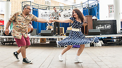 © Licensed to London News Pictures. 28/06/2015. London, UK. Members of the public dancing as Devil's Cut Combo is on stage at the Swing East jump 'n' jive jamboree in Chrisp Street Market in London's East End.  Revellers gathered together in vintage clothing to celebrate fifties music and dance, lots and lots of dance. Photo credit : Stephen Chung/LNP