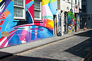 Pedestrians walk through graffiti's streets in Shoreditch, London<br /> Shoreditch, an area that was dominated by light industry is now home to creatives and the streets are decorated with a good deal of graffiti - much by established street artists
