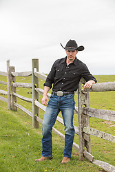 hot cowboy by a rustic fence on a ranch