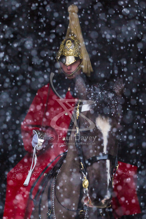 A member of the Household Cavalry is partially obscured by snow as a flurry hits Westminster at Horseguards. Westminster, London, February 27 2018.