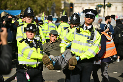 © Licensed to London News Pictures. 10/10/2019. London, UK. Police move in to remove Extinction Rebellion activists from the roads around Trafalgar Square in Westminster, central London, who are protesting for a fourth day running. The climate change group have blockaded the Westminster area, demanding that the government takes immediate and decisive action on climate change. Photo credit: Ben Cawthra/LNP