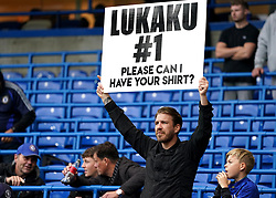 A Chelsea fan holds up a sign for Chelsea's Romelu Lukaku shirt before the Premier League match at Stamford Bridge, London. Picture date: Saturday October 2, 2021.