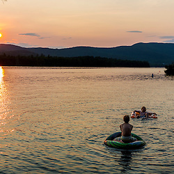 Boys playing catch while floating in Squam Lake. Holderness, New Hampshire.