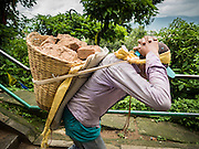 31 JULY 2015 - KATHMANDU, NEPAL: A laborer carries brick down the hill from Swayambhunath, also known as the Monkey Temple. It's a complex of Buddhist and Hindu temples in Kathmandu. It was heavily damaged in the Nepal Earthquake. The Nepal Earthquake on April 25, 2015, (also known as the Gorkha earthquake) killed more than 9,000 people and injured more than 23,000. It had a magnitude of 7.8. The epicenter was east of the district of Lamjung, and its hypocenter was at a depth of approximately 15 km (9.3 mi). It was the worst natural disaster to strike Nepal since the 1934 Nepal–Bihar earthquake. The earthquake triggered an avalanche on Mount Everest, killing at least 19. The earthquake also set off an avalanche in the Langtang valley, where 250 people were reported missing. Hundreds of thousands of people were made homeless with entire villages flattened across many districts of the country. Centuries-old buildings were destroyed at UNESCO World Heritage sites in the Kathmandu Valley, including some at the Kathmandu Durbar Square, the Patan Durbar Squar, the Bhaktapur Durbar Square, the Changu Narayan Temple and the Swayambhunath Stupa. Geophysicists and other experts had warned for decades that Nepal was vulnerable to a deadly earthquake, particularly because of its geology, urbanization, and architecture.        PHOTO BY JACK KURTZ