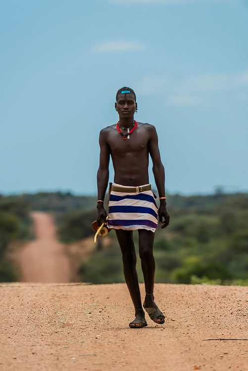 Hamer tribe man walking up a long dirt road in the Omo Valley, Ethiopia.
