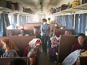 A controller makes her way through a dusty wagon. She wears a mask to avoid breathing the hudst and sand. Life inside the train - mostly Muslim Uighur people  ride this train.