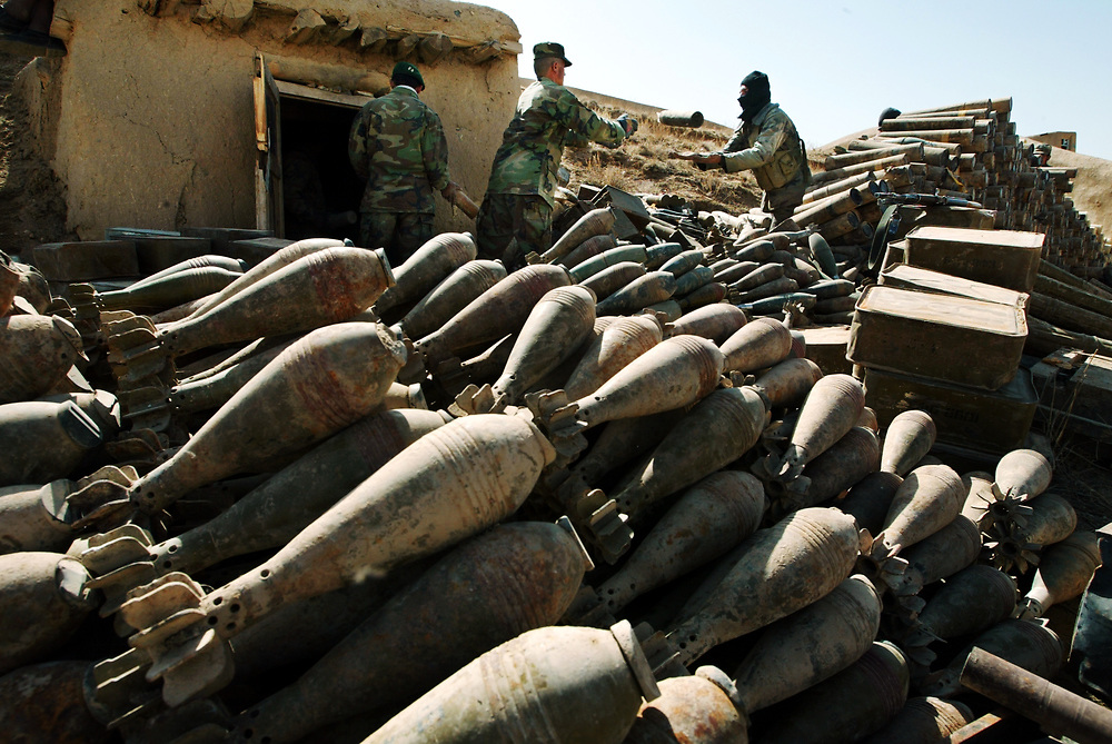 """2/24/04 -- SPECIAL FORCES A-TEAM -- ORUZGAN PROVINCE, AFGHANISTAN --  With hundreds of 82mm mortars already removed and stacked outside bunkers, soldiers of the newly formed Afghan National Army, 1ST Company of the First Battalion, Third  Brigade led into the Oruzgan Province by an A-TEAM with the 3rd Special Forces Group toss an 82mm mortar to each other while removing nearly ten tons of munitions from a bunker complex under the Oruzgan district. Special Forces A-Team and officers of the Afghan National Army, 1ST Company of the First Battalion, Third  Brigade spent an entire day and night applying  """"Afghan Diplomacy"""" by drinking many glasses of tea and finally asking what is behind the locked doors in the bunkers below. Ubai Dullah's response was, """"Nothing for soldiers.....just some bullets....""""  After initial inspection of the bunkers, nearly ten tons of mortars, rockets, land mines and ammunition were found in the bunkers.  Negotiations between the district chief and the A-Team came to brief but tense """"stand off"""" as soldiers began to remove the weapons when the district chief called in armed militia. Between talks and calling in an U.S. Air Force B-1 Bomber to make low passes over the valley, matters were resolved with some ammunition allowed to stay in the hands of the district chief but all mortars and rockets had to be surrendered. (Photo by Jack Gruber, USA TODAY)"""